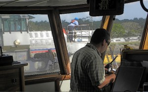 Canal pilot Erick Hendricks works on the bridge as a mule glides alongside.