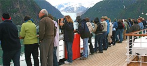 Passengers line the rail to view Alaskan glaciers, but this ship is so large, it is miles from the nearest glacier.