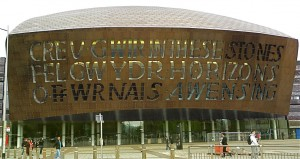 "The spectacular Wales Millennium Center dominates the revamped Cardiff Bay cityscape. Poet Gwyneth Lewis wrote, in Welsh, ""Creating truth like glass, from the furnace of inspiration,'' and in English, ""In these stones, horizons sing.'' The metal facade is stainless steel, tinted with bronze oxide."