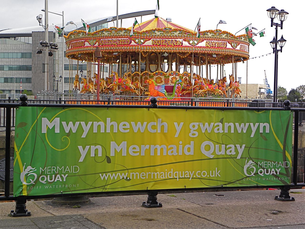 """The carousel is a touch of whimsy amid the modern architecture in renovated Cardiff Bay. In Welsh, the banner advises, """"Enjoy the spring in Mermaid Quay'' -- the name of the restaurant and entertainment complex."""