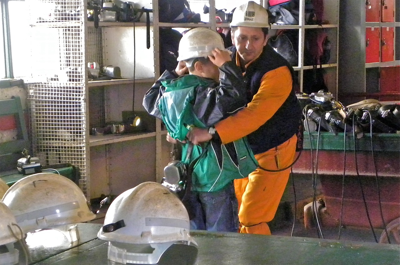 A former miner suits up a child for the trip 300 feet down, at the Big Pit Museum.