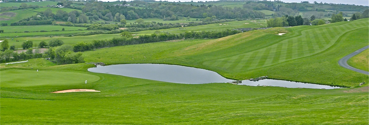 The 18th green slopes back toward the approach; an approach shot hit too short is likely to roll into a pond.